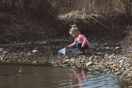 Little girl launches paper boats down the creek in spring