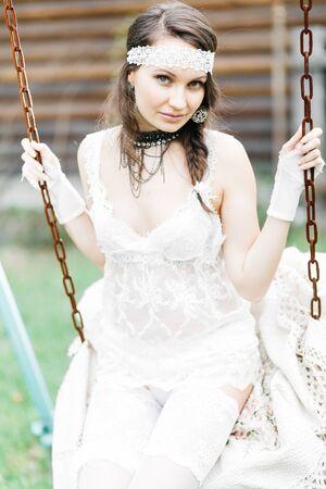 Tender girl in a white dress in the flowers of bird cherry