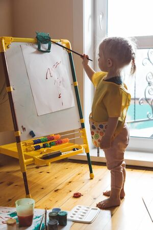Little girl sits on the floor and draws on an easel Stok Fotoğraf