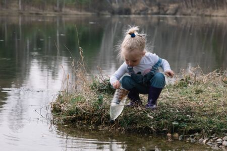 Little girl catches and feeds fish