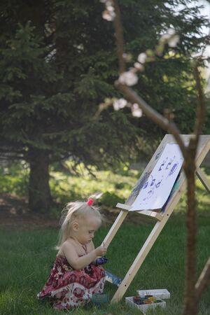 Little girl in nature paints on an easel under a blooming cherry Imagens