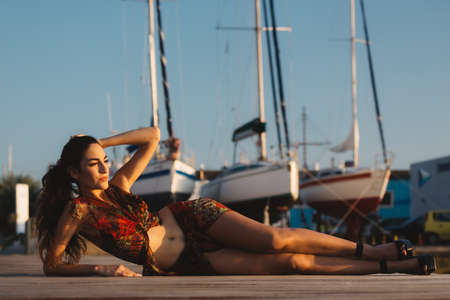 Girl in a beach suit in front of boat
