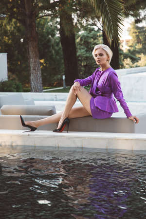 Young woman in purple dress near fountains in the garden