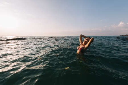 Girl with long hair swims in the sea, splashes water on a background of a sunset sky