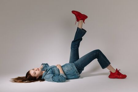 Girl in jeans and red sneakers posing on a white background Standard-Bild - 147774634