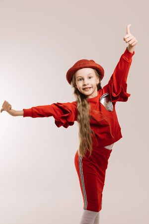 Little girl in a red suit and hat posing on a light background