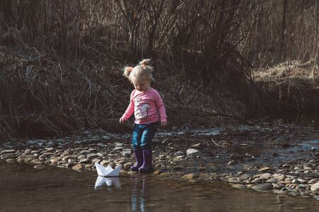 Little girl in rubber boots launches paper white boats in creek in spring or autumn. Banque d'images