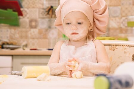 Little girl cooks at home in the kitchen