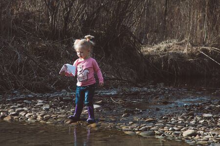 Little girl in rubber boots launches paper white boats in creek in spring or autumn