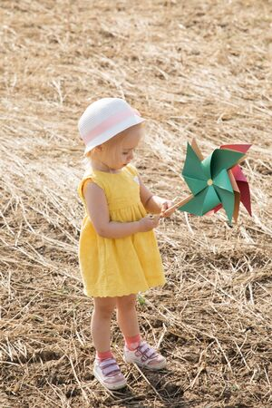 Little girl in yellow dress and hat in a field with paper windmills