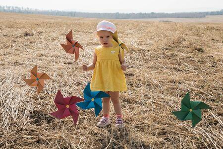 Little girl in yellow dress in a field with windmills Foto de archivo