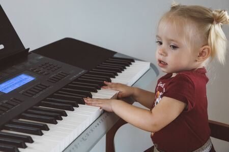 A little girl in a burgundy suit plays a synthesizer