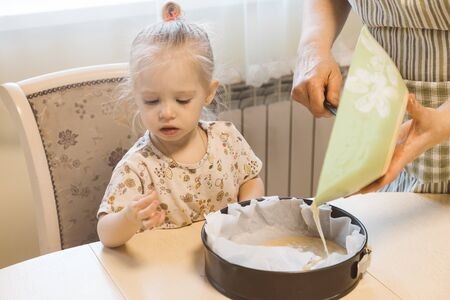 A baby cooking with grandmother and tasting sweet dough