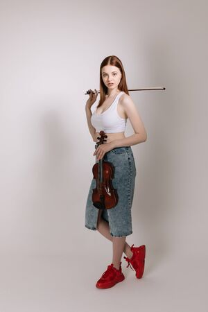 The girl in jeans and red sneakers plays the violin on a white background
