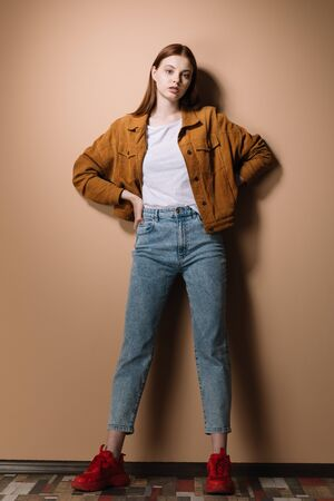 Girl in jeans and a brown jacket posing on a beige background