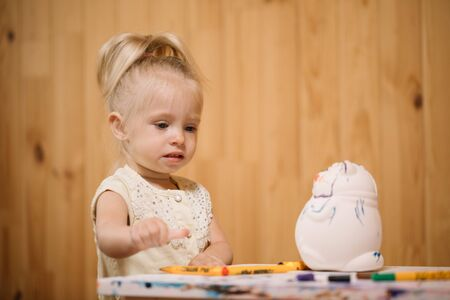 Little girl paints a piggy bank with markers