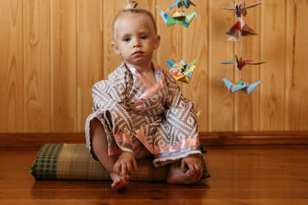 Little girl in kimono sits on tatami