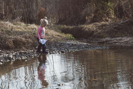 Little girl in rubber boots launches paper white boats in creek in spring or autumn.