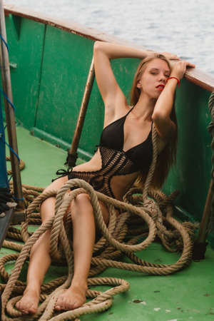 Girl with long hair in a black swimsuit posing on a fishing boat at sea.