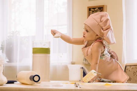 Little girl in a cap and apron cooks in the home kitchen Standard-Bild