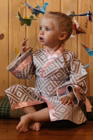 Little girl in kimono sits on tatami on the background of Japanese origami cranes Standard-Bild
