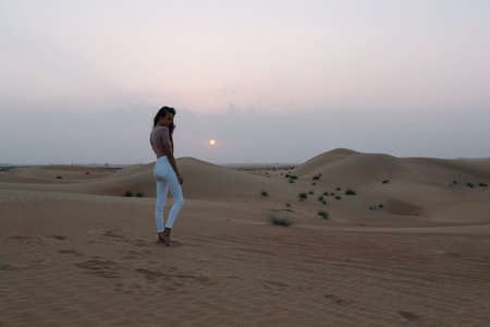 A girl in a white pants poses on the sand in the desert