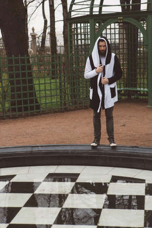 Man in black and white robes near a chess fountain in a city park