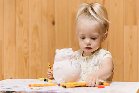 Little girl paints a clay piggy bank in the form of a fat cat with color markers on a wooden wall background