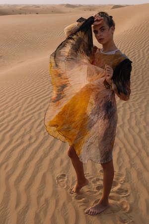 A girl in a light dress poses on the sand in the desert