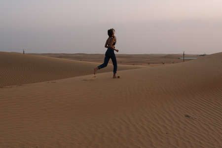 A girl in jeans poses on the sand in the desert Standard-Bild