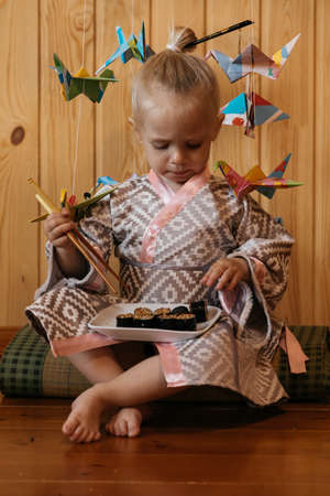 Little girl in kimono sits on a tatami and eats sushi with chopsticks on the background of Japanese origami cranes