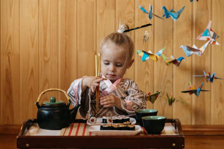 Little girl in a kimono eats sushi on the background of Japanese origami cranes