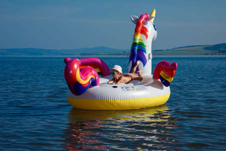 Baby girl swimming on white, trendy, blown up beach unicorn in summer in the sea