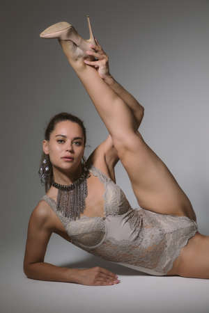 Fashion flexible girl gymnast in high heels in acrobatic positions