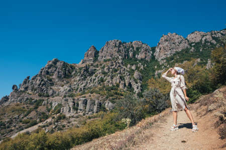 Young woman, girl tourist in safari dress on the rocks in the mountains on a background of blue sky