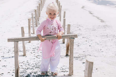 Little girl dressed in a pink dress in Asian style on the background of the salt lakes of the Dead Sea or pink lake