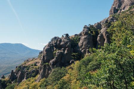 A ridge of brown rocks covered with greenery against a blue sky on the Black Sea coast Zdjęcie Seryjne