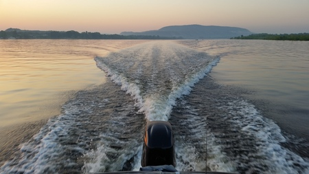 Dawn on the boat while driving the spray from the motor
