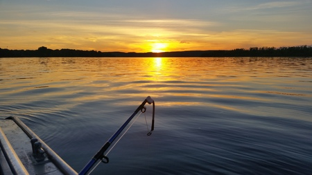 A meeting of a beautiful dawn on a river in the summer on a boat with a fishing rod