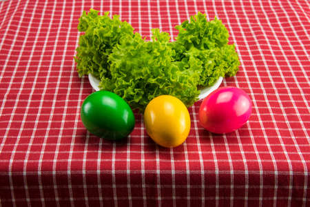 Easter eggs and fresh green salad on red white checkered tablecloth. Health concept. Stock Photo