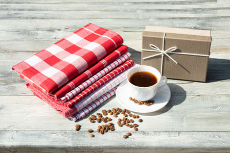 Greeting card. Birthday giftbox with white cup of black coffee with roasted beans togehter with a stack of tableclothes on rustic bright wooden table. Outdoor. Card concept. Banco de Imagens