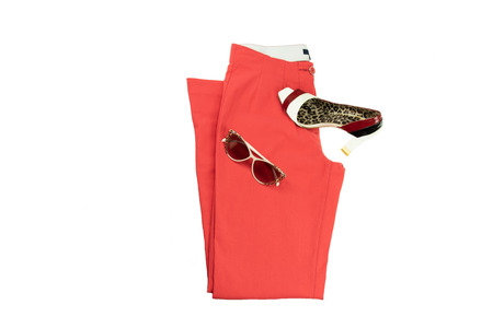 Red elegant woman trousers, an matching elegant female shoe and a fashionable sunglasses  on it.  Fashion concept. Isolated on white.