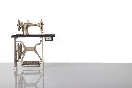 Beautiful miniature model of a vintage sewing machine on bright table isolated on white background. Advertisement for tailor business. Space for text and montage. Stock Photo