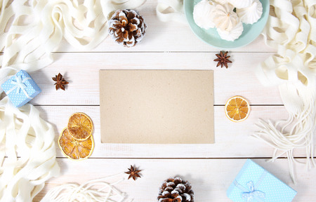 Autumn or winter composition with top view on paper sheet, white scarf, gift box and other winter accessories. Copy space blank sheet.