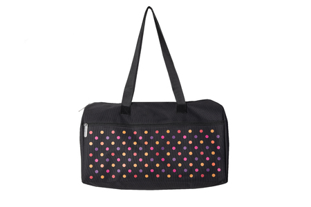 Bags fashion. Closeup of multicolored dotted overnight bag on a white background. Travel concept.