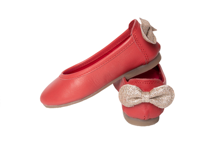 Red shoes. Closeup of red girls shoes with a golden bow isolated on a white background. Fashionable footwear.