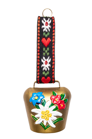 Switzerland souvenir. Closeup of colorful swiss cow bell with Edelweiss and gentian isolated on a white background. Macro.
