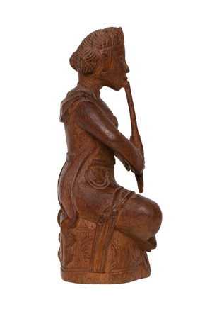 Close-up of  antique carved wooden figurine or sculpture from a asian man is sitting and playing a music instrument. Carved sculpture is isolated on white background. Macro.