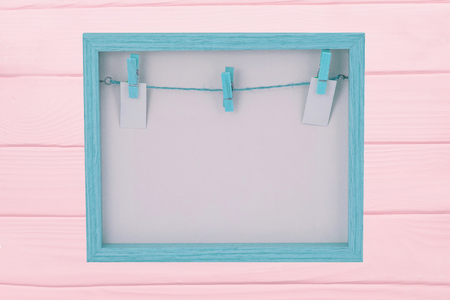 Empty wooden frame. Close-up of empty blue wooden frame with a clothesline and clothespins on background of frame Isolated on a pink board . Food recipe, valentine, mothers day or other festivals. Macro.