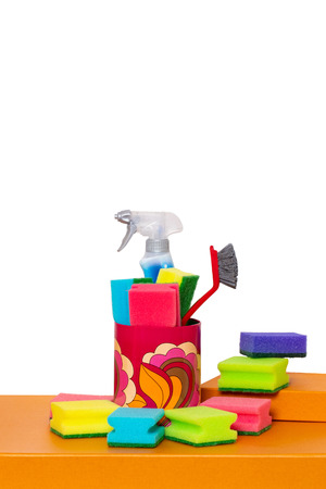 Spring cleaning background. Close-up of house cleaning products and cleaning supplies on orange wooden table isolated on a white background. Household chore concept. Macro.